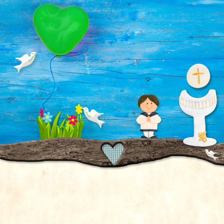 First Holy Communion invitation, child praying, holy grail flowers and globe on blue wooden background and blank space for write message