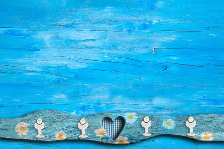Primeras invitaciones de la comunión santa, cáliz, corazón en fondo de madera azul con el espacio vacío para el texto y las fotos. Foto de archivo - 77464122