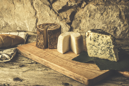 Wooden board on table with different types of Spanish cheese. Фото со стока - 86756483