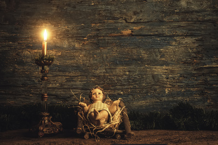 Christmas card, Child Jesus in his crib and candle on  dark wooden background with copy space.