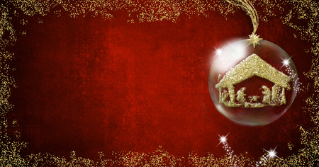 Background for writing christmas cards, Nativity Scene freehand in gold metallic texture inside xmal ball on red background with space for message, panoramic format.