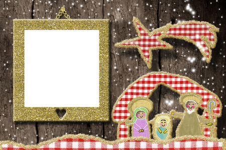 Christmas photo frame greetings card. Cute  Nativity Scene made with cheerful cuts of fabrics and golden glitter and empty picture frame hangin on rustic wooden wall.