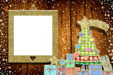 Christmas empty photo frame greeting card.  Christmas tree and gifts made with cheerful cuts of fabrics and golden glitter, gold glitter empy photo frame on old wooden wall.