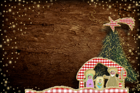 Cute Christmas Nativity Scene  greeting card. Nativity Scene made with cheerful cuts of fabrics and golden glitter on old wooden background with copy space.