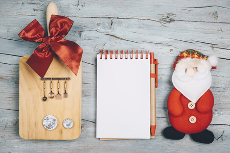 Fun background for the Christmas menu or recipes. Blank notebook, cutting board with utensils and miniature dishes and Santa Claus doll. Imagens