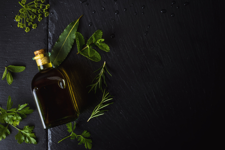 Flavored virgin olive oil in a glass bottle and olives,herbs, laurel, rosemary, parsley, mint on black stone slate, top view and copy space. Banque d'images - 123610954