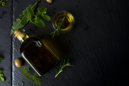 Flavored virgin olive oil in a glass bottle and olives,herbs, laurel, rosemary, parsley, mint on black stone slate, top view. Banque d'images - 123610953