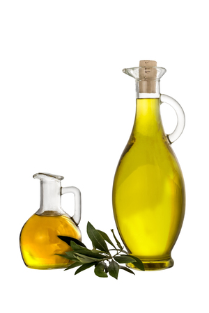 Extra Virgin olive oil in two glass rustic bottles and leaves isolated over a white