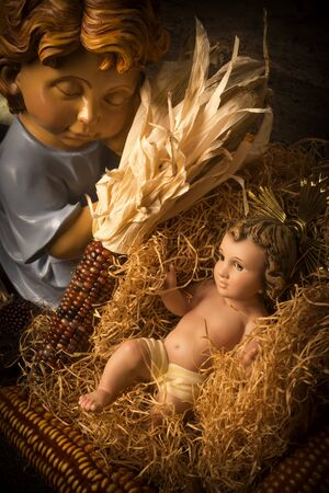 Christmas cards. Baby Jesus care by an angel in a crib made from corn cobs.Vertical image.