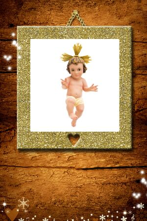 Christmas greeting card, Baby Jesus vintage figurine in gold picture hanging on a wooden wall. Stock Photo