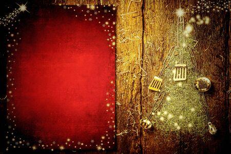 Hintergrund laden ein, Weihnachtsmenü zu schreiben. Alte Küchenutensilien, die einen Weihnachtsbaum und leeres rotes Papier auf altem hölzernem Hintergrund bilden. Standard-Bild