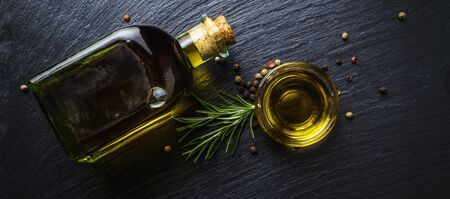 Extra virgin olive oil in a glass bottle, flavored with rosemary and peppercorns on black stone slate Reklamní fotografie - 137800578