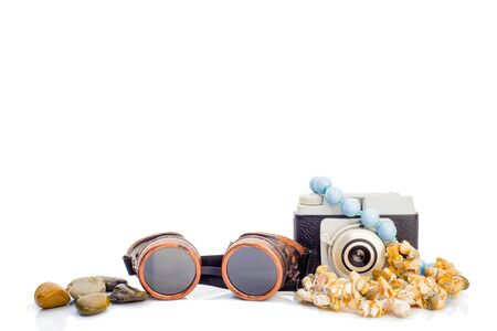 Summer holidays objets isolated on white background, retro photo camera, vintage airplane pilot glasses, sea shell necklace and beach stones Banco de Imagens