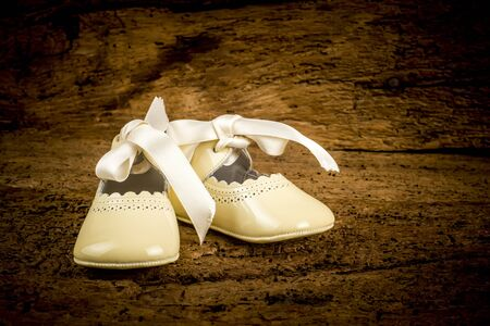 Small newborn patent leather shoes with bow on old wooden background, traditional christening wardrobe.