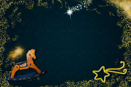 Children's Christmas background. Rocking horse, Bethlehem star and gold glitter on dark blue background with empty space to put photos and text