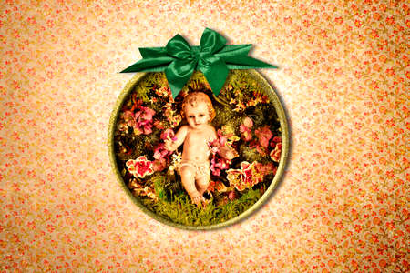 Baby Jesus Vintage Christmas Postcard. Photograph of baby jesus in a gold frame with green bow on vintage style wall 免版税图像