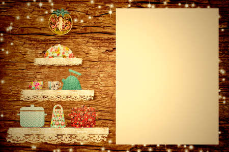 Christmas menu border background. Adorable christmas tree made with fabric cutouts and lace, pots, teapot, saucepan and blank parchment to write xmas menu on old wooden wall.