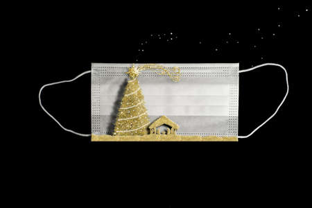 Christmas Covid-19 greeting card. Surgical mask for the covid decorated with the manger and Christmas tree in freehand gold glitter on black background with space for message