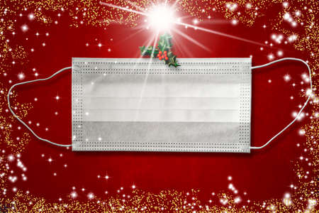 Christmas covid-19 greeting card. White surgical mask with holly leaves and stars on a red background. Concept use of mask for coronavirus, emty space to write.