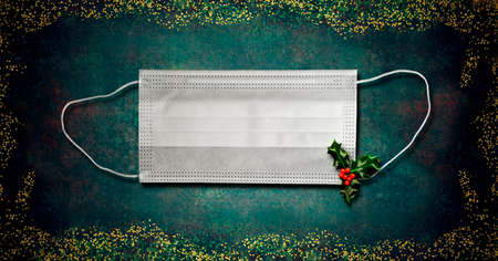 Christmas covid-19 greeting card. White surgical mask with holly leaves on a green background and gold glitter border.Concept use of mask for coronavirus, panoramic format.