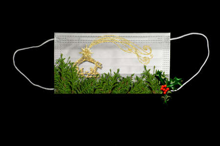 Christmas Covid-19 greeting card. Awareness of wearing the mask at Christmas concept. Surgical mask with fir branches, holly and manger in gold, blank space to write message