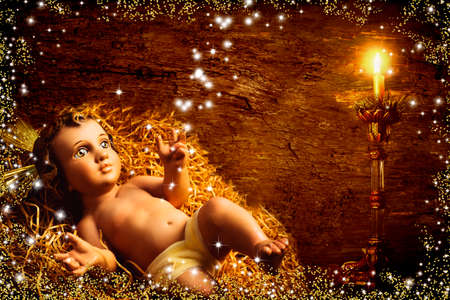 Christmas Child Jesus traditional greeting card. Baby Jesus in his straw cradle and bright lit candle on old wooden background with stars and gold glitter 免版税图像