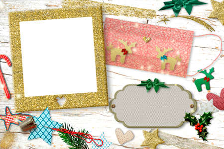 Christmas greeting with photo frame in times of coronavirus. COVID-19 face mask customize with two gold glitter reindeers, needle, thimble, ornaments and an empty photo frame on an old wooden table. Copy space to write, diy concept.