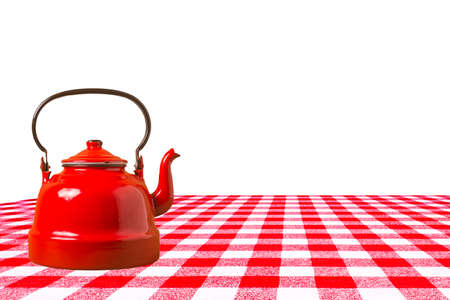 Oldred teapot on a table with red checkered tablecloth isolated on white background