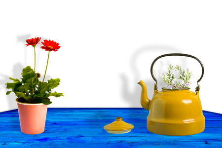 Yellow teapot with sprigs of rosemary and red daisy gerbera flowers in a pot on a mediterranean blue wooden table with blank space for design 免版税图像