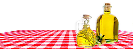 Extra virgin olive oil. Olive oil flavored with rosemary in a jar and olive oil in a rustic glass bottle on a table with a red checkered tablecloth on a white background. Panoramic image 免版税图像