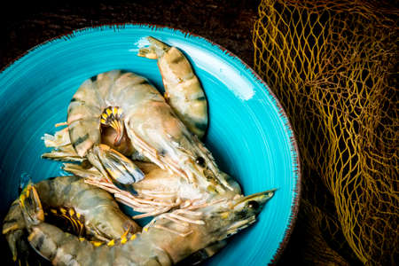 Fresh tiger prawns on a blue plate and dark background with fishing net 免版税图像