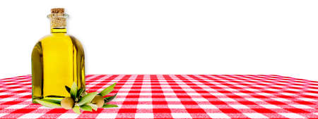 Bottle of extra virgin olive oil, olives and branch on red checkered tablecloth isolated on white background, panoramic image.