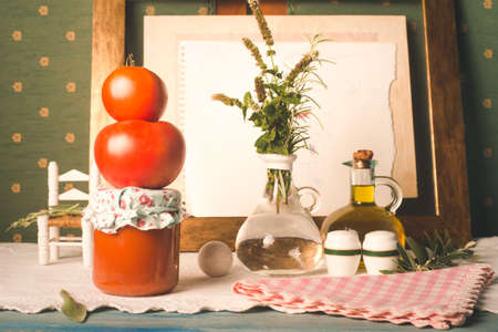 Homemade canned fried tomato. Raw organic tomatoes, fried tomato in glass bottle and olive oil in an old elegant kitchen
