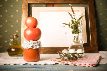 Homemade fried canned tomato. Raw organic tomatoes, fried tomato in glass bottle and olive oil in a vintage home. 免版税图像