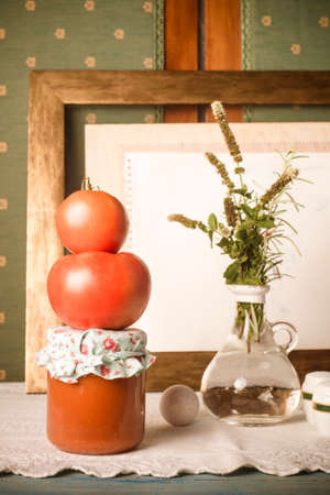 Homemade canned tomato. Raw organic tomatoes, fried tomato in glass bottle in an old kitchen, vertical image. 免版税图像
