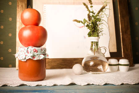 Homemade canned tomato. Raw organic tomatoes, fried tomato in glass bottle in an old kitchen
