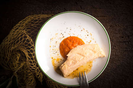 Chunk of northern tuna albacore canned with olive oil on a plate with homemade tomato sauce on a dark rustic background