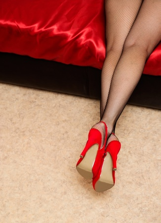 girl lying on the bed in stockings in red shoes photo