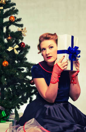 Woman sitting near a Christmas tree with gift in hand Stock Photo - 11572052