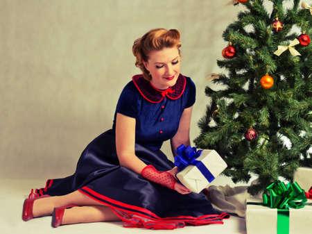 pin up vintage: Donna seduta vicino a un albero di Natale con il regalo in mano Archivio Fotografico