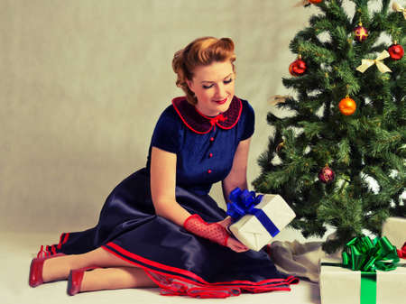 Woman sitting near a Christmas tree with gift in hand photo