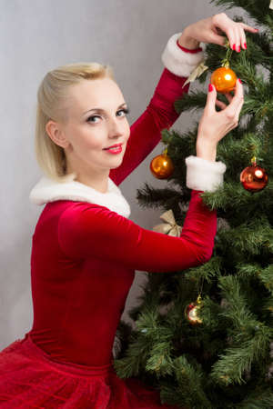 Woman sitting near a Christmas tree with balls in hand photo
