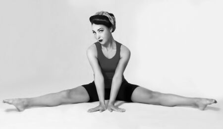 splits: Famous retro pose foto. brunette in a blue shirt with a scarf on her head and hair in a retro style sitting on the splits