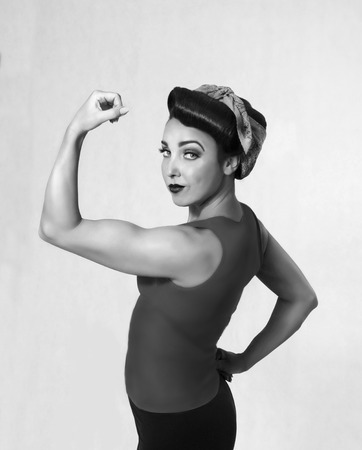 showoff: woman brunette in a blue shirt with a scarf on her head and hair in a retro style biceps show-off Stock Photo