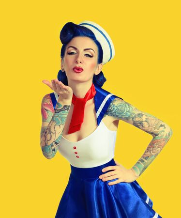 as: beautiful girl dressed as sailors with tattoos, sends a kiss