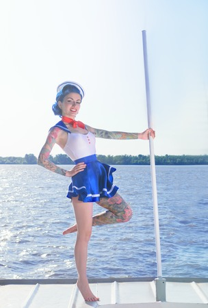 pinup girl: Pin-up girl in a sailor suit with a tattoo is on the ship