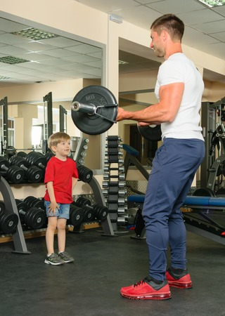 Pope shows little son how to lift weights in the gym Reklamní fotografie