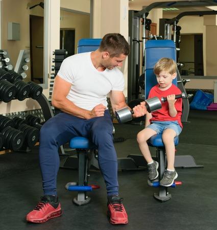 levantar pesas: Papa muestra pequeño hijo cómo levantar pesas en el gimnasio Foto de archivo