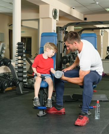 instance: Pope shows little son how to lift weights in the gym Stock Photo