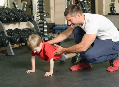 Pope shows little son how to lift weights in the gym Stock Photo